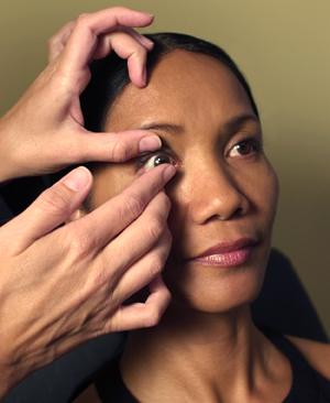 Hands putting contact lens in woman's eye.