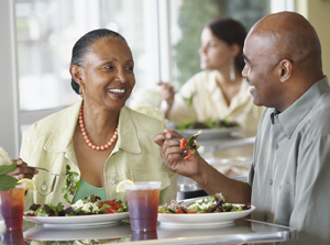 Man and woman sitting in restaurant eating salads.