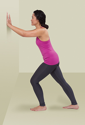 Woman pressing hands against wall and stretching calf muscles.